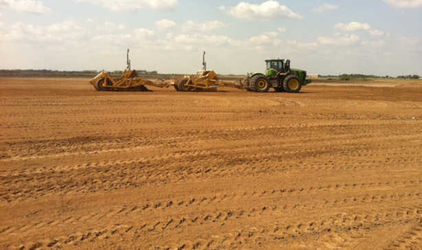 Green tractor pulls two land levelers across brown dirt field