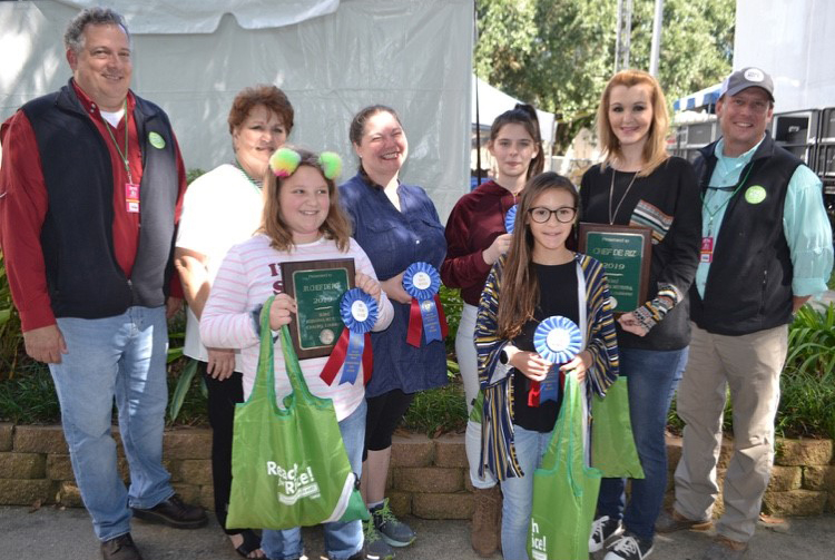 "Group shot of children and adults holding prize ribbons and green bags that say ""Reach for Rice!"""