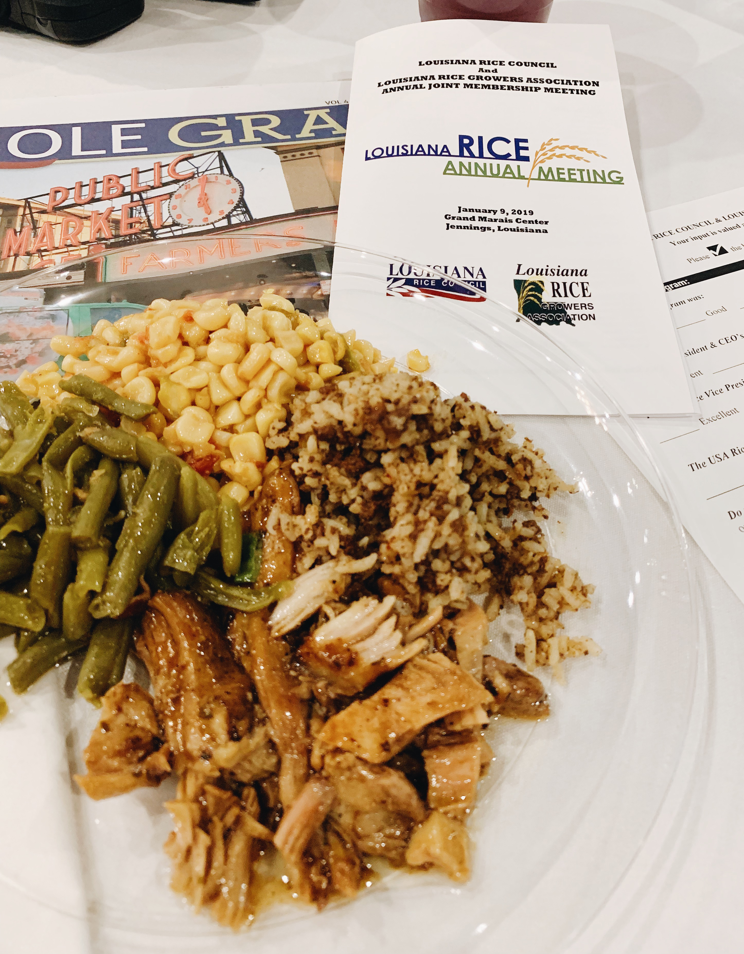 LA rice meeting program on table next to plate full of rice, green beans, corn, and stewed chicken