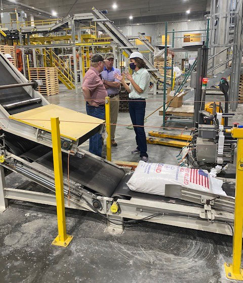 Three people stand near bagging line in factory