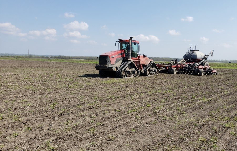 Red drill seeding equipment plants rice in new dirt field
