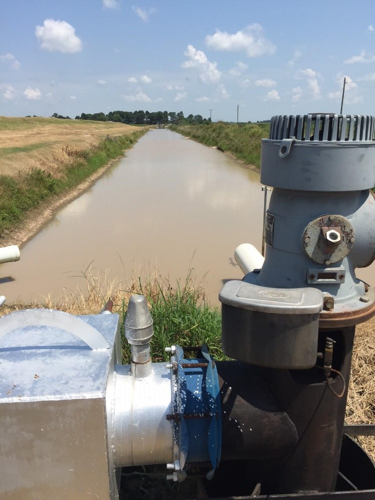 Re-Lift pump on irrigation canal in foreground, canal stretches out to grove of trees in background