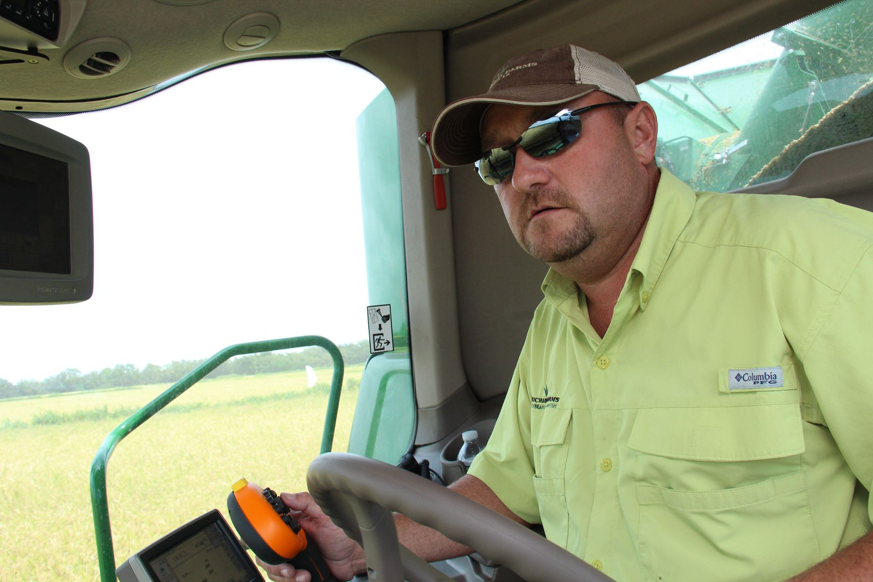 Man wearing yellow shirt and sunglasses drives green combine