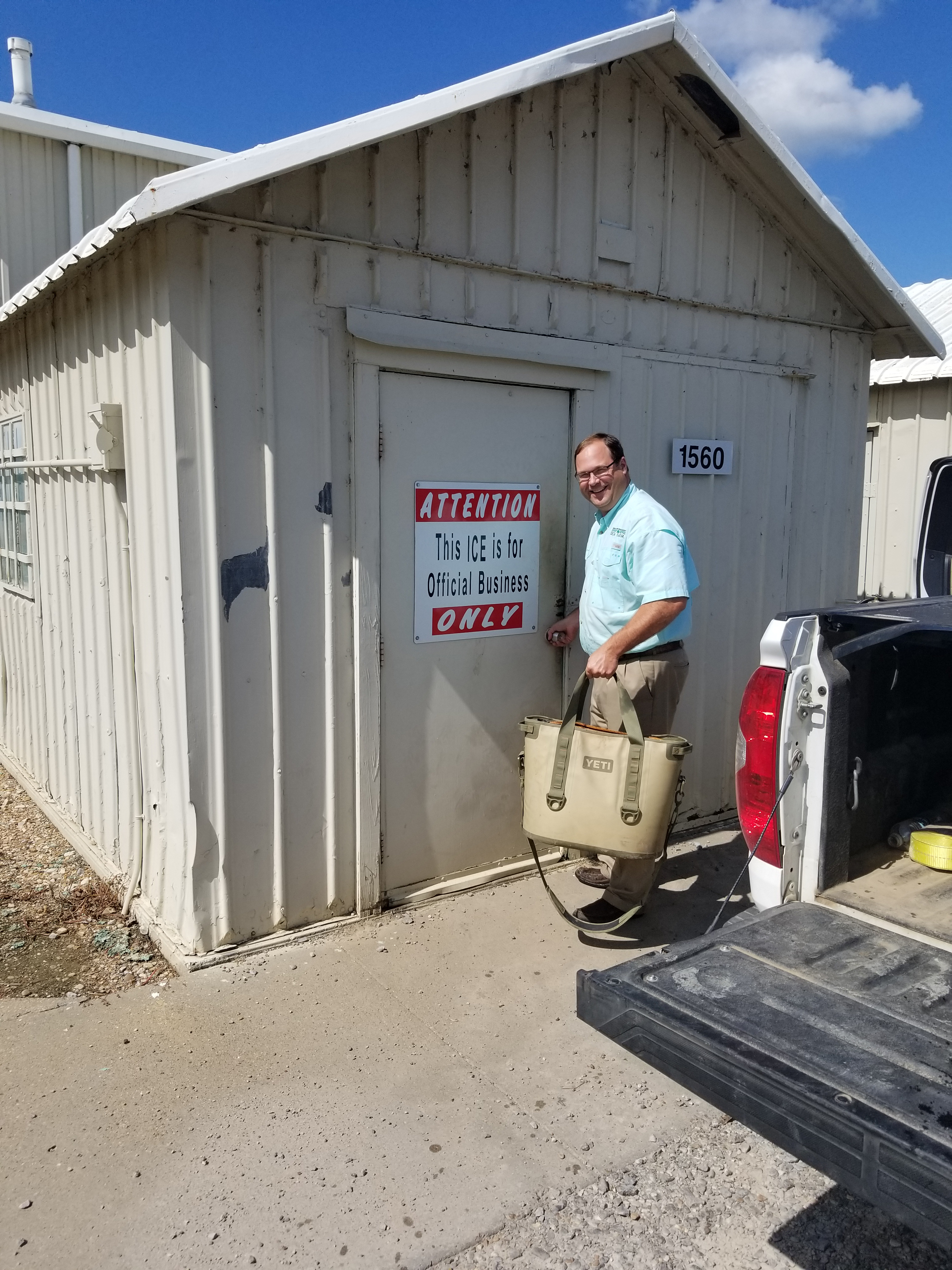 Trey Cooke opens door to an ice shed, carrying a Yeti cooler