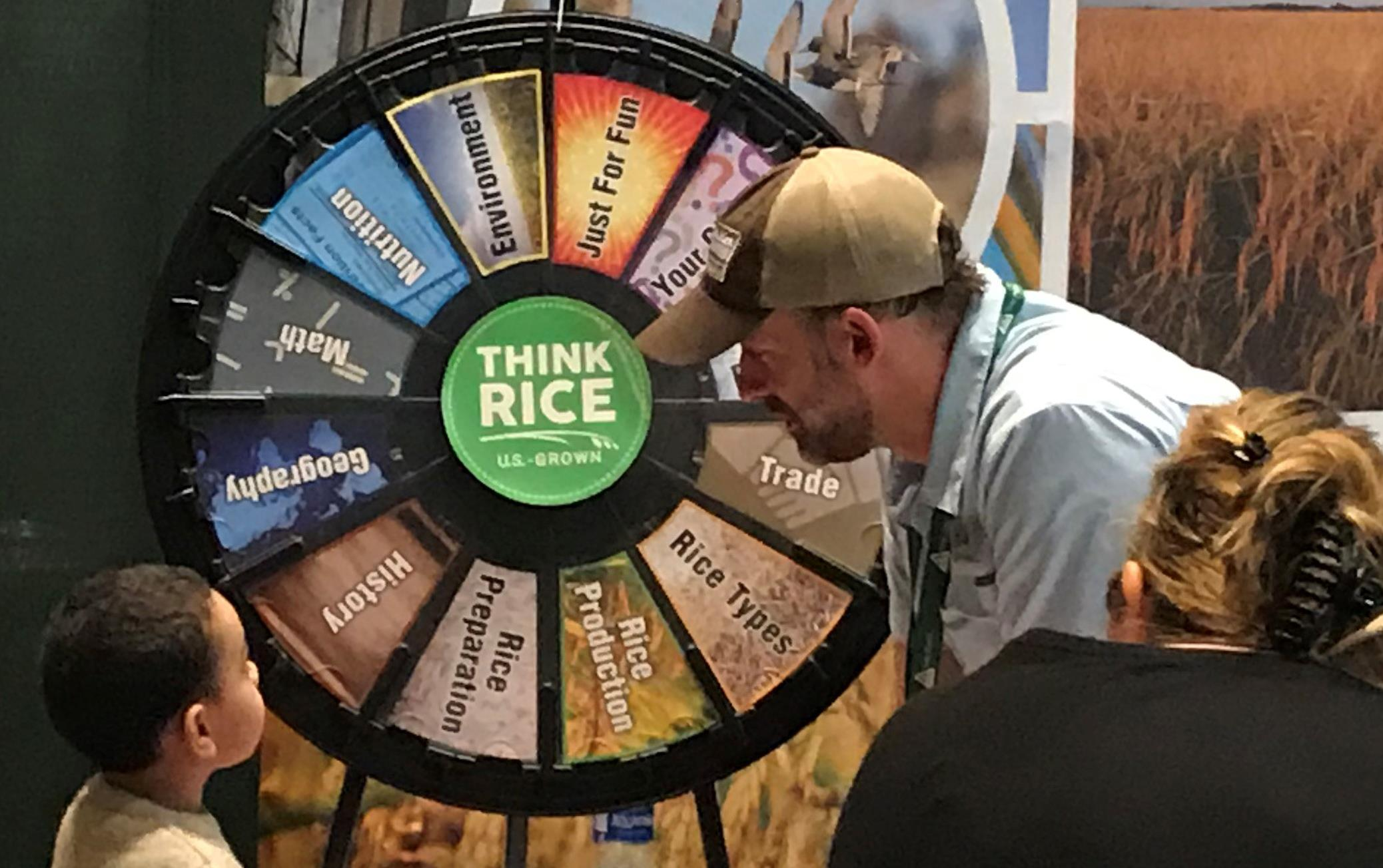 Children line up for their chance at the Think Rice trivia wheel sitting on a table draped in an American flag tablecloth, man wearing ballcap leans over to talk to small boy getting ready to spin the wheel