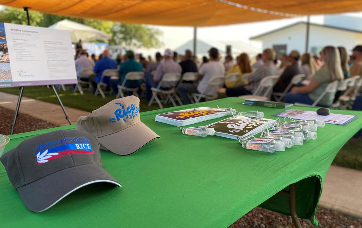 2021-CA-Field-Day,-swag-table in front of attendees sitting in chairs under a tent