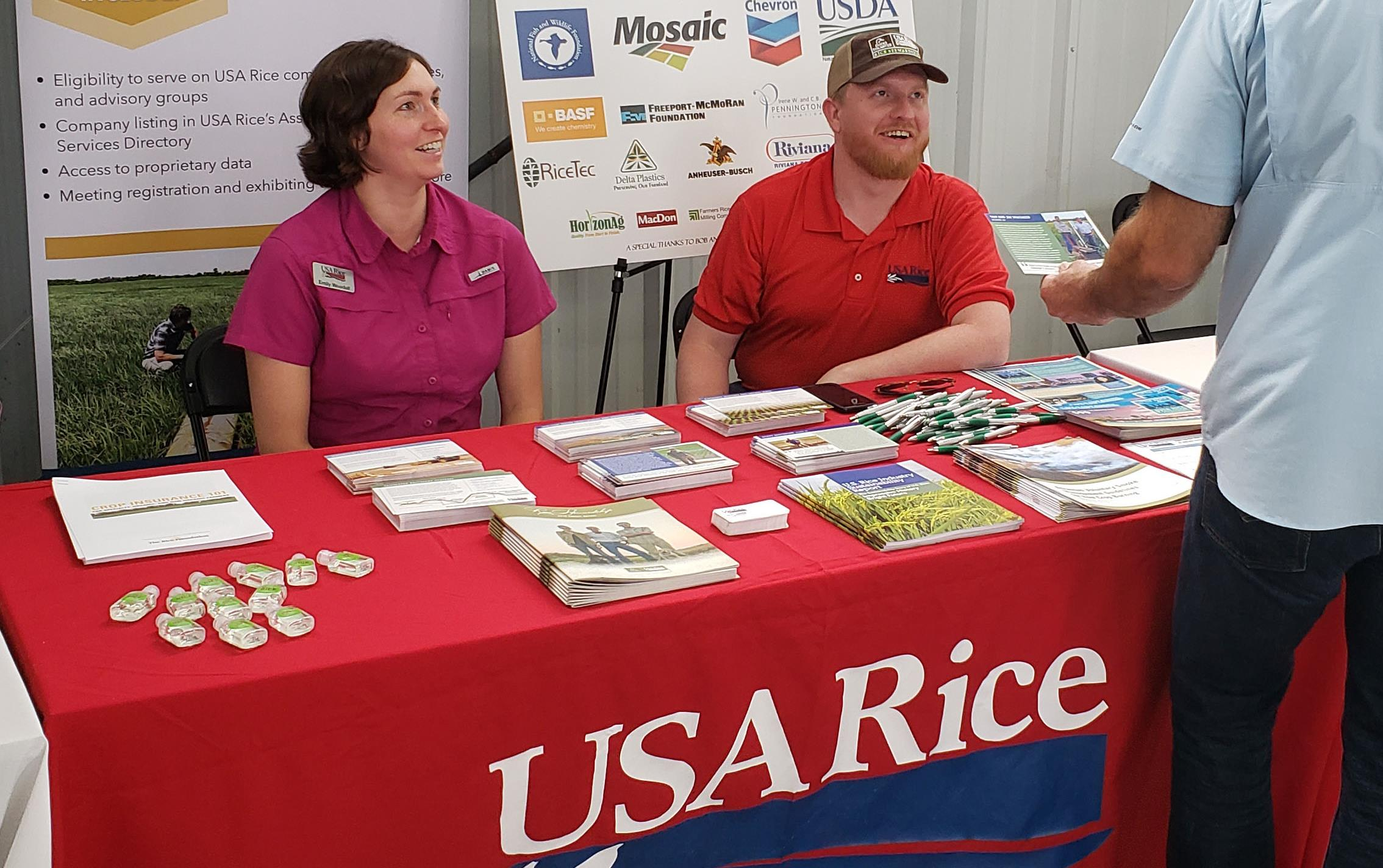 A woman and a man sit behind a table draped with USA Rice tablecloth and covered with literature, man stands in front holding postcard, posters in background