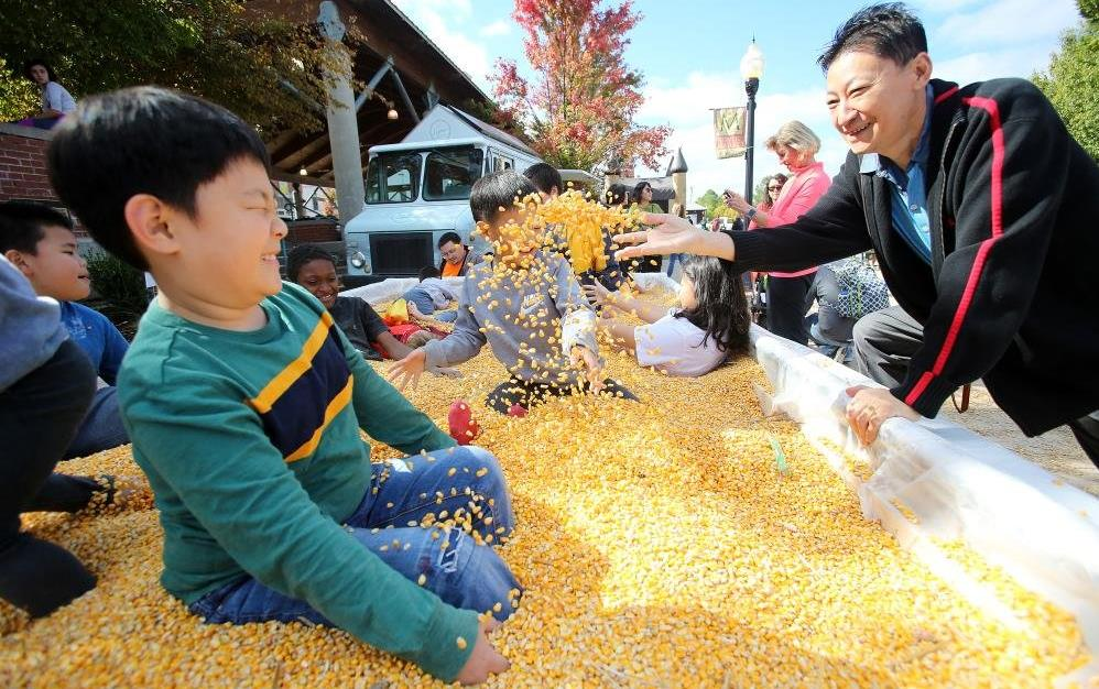 Children play in a large container filled with yellow corn, woman throws corn in the air