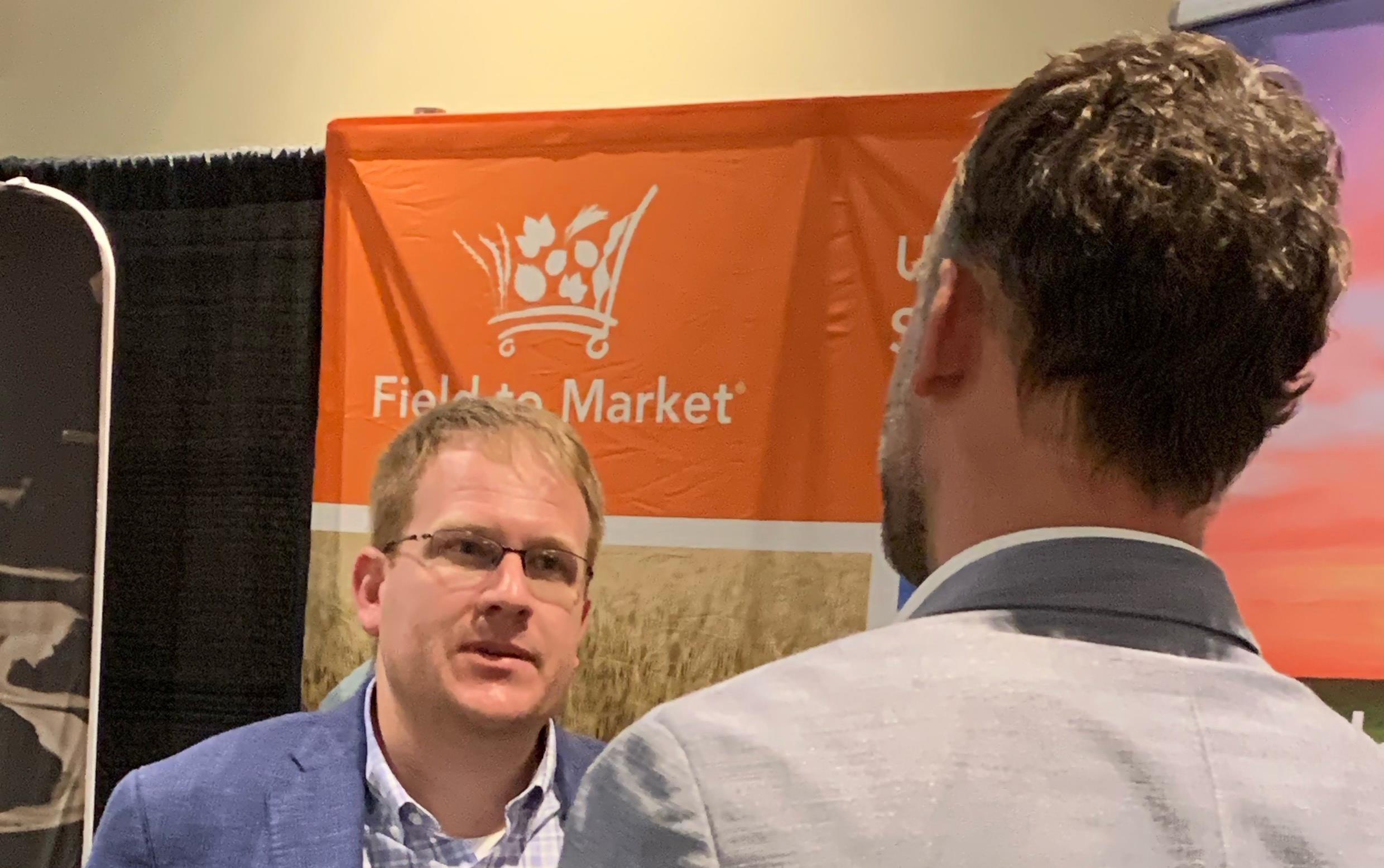 Two men stand in front of orange banner that reads: Field to Market