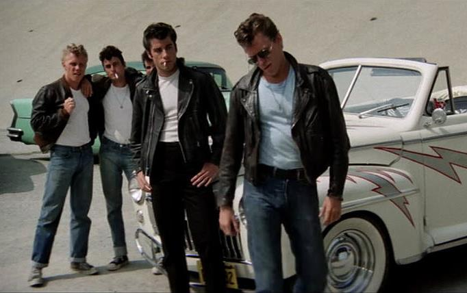 "From the movie ""Grease,"" boy gang in leather jackets, girl gang in pink jackets stand around souped up roadster"