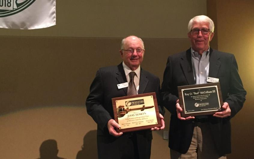 Producers Rice Mill 75th Anniversary, retirees hold plaques standing under anniversary banner