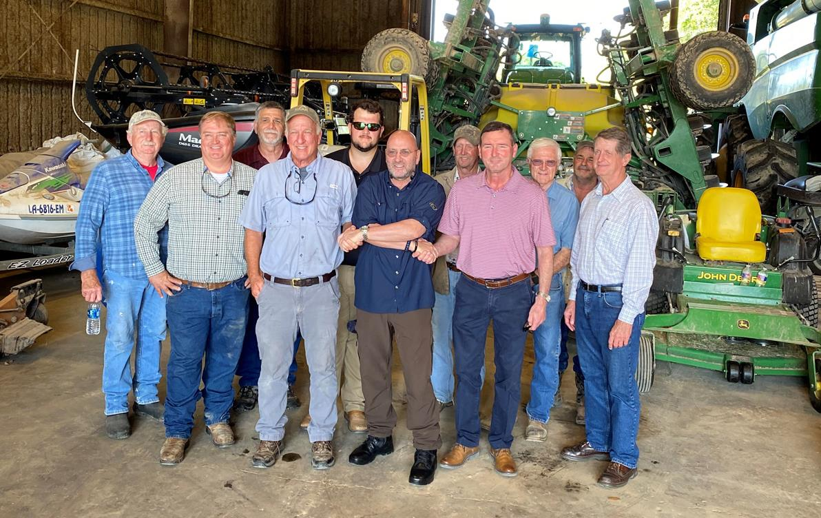 Group of men stand in farm shop in front of farming equipment
