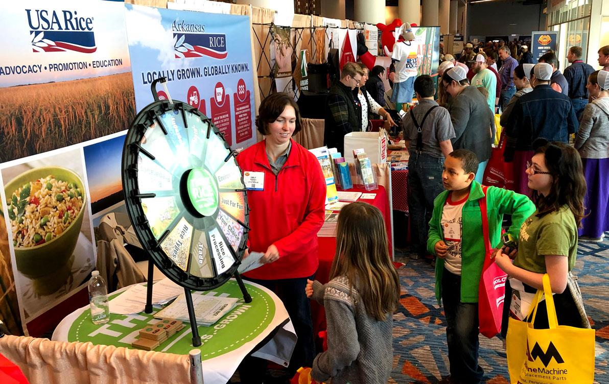 Woman wearing red shirt stands in exhibit booth in front of children gathered around spinning Rice Wheel