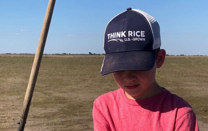 Young boy wearing jeans, red shirt, and ThinkRice ballcap kneeling in planted field, holding new rice plant