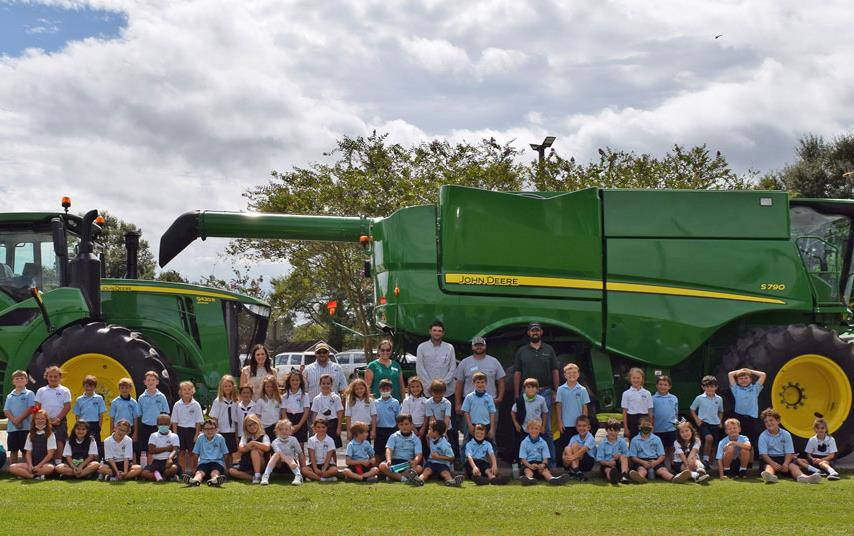 Elementatry school students pose for group shot in front of green combine