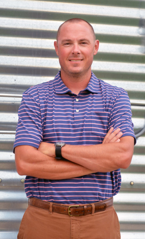 Matthew Feilke, AR rice farmer stands with arms folded in front of metal grain bin wearing purple striped shirt and brown pants