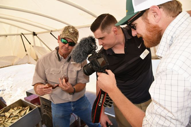 Cameraman films man in ball cap and sunglasses holding two crawfish while another man wearing a black shirt looks on