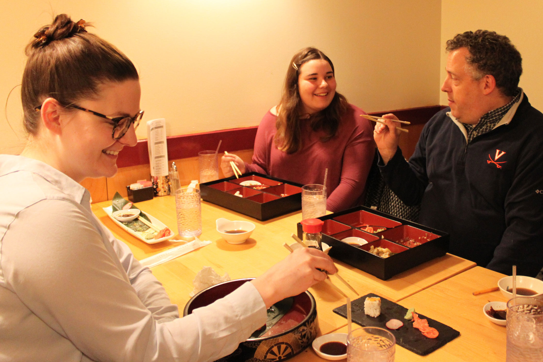 People using chopsticks to eat sushi at a restaurant
