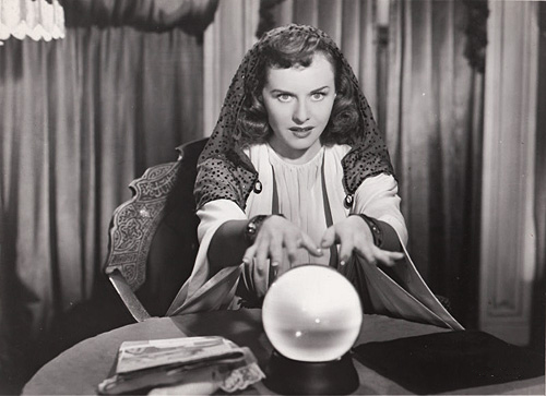 Female fortune teller with her hands over a crystal ball