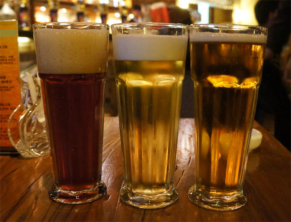 Bird-Friendly-Beer, three full glasses of beer on a bar