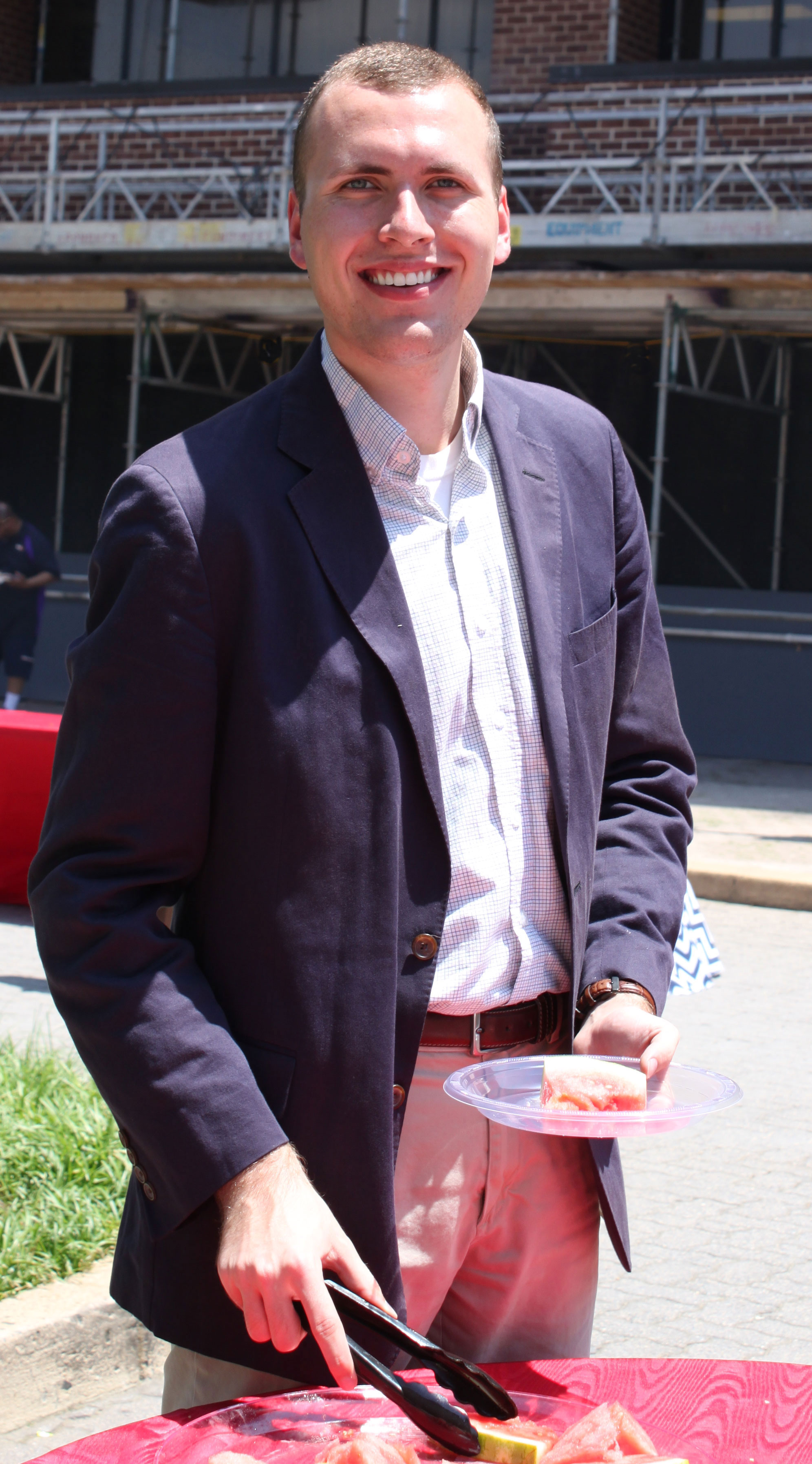 USA Rice intern Ethan-Cartwright eats watermelon at building cookout