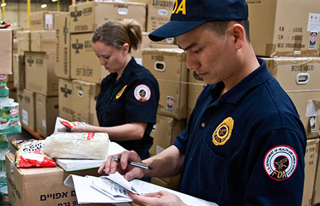 FDA inspectors holding clipboards in warehouse filled with boxes of food products