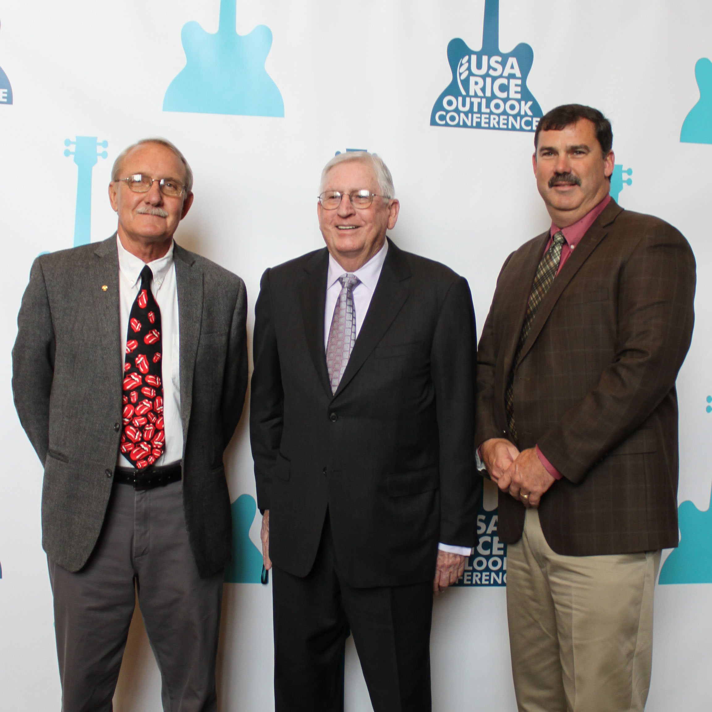Three Rice-Award-Winners stand in front of 2016 Outlook step and repeat