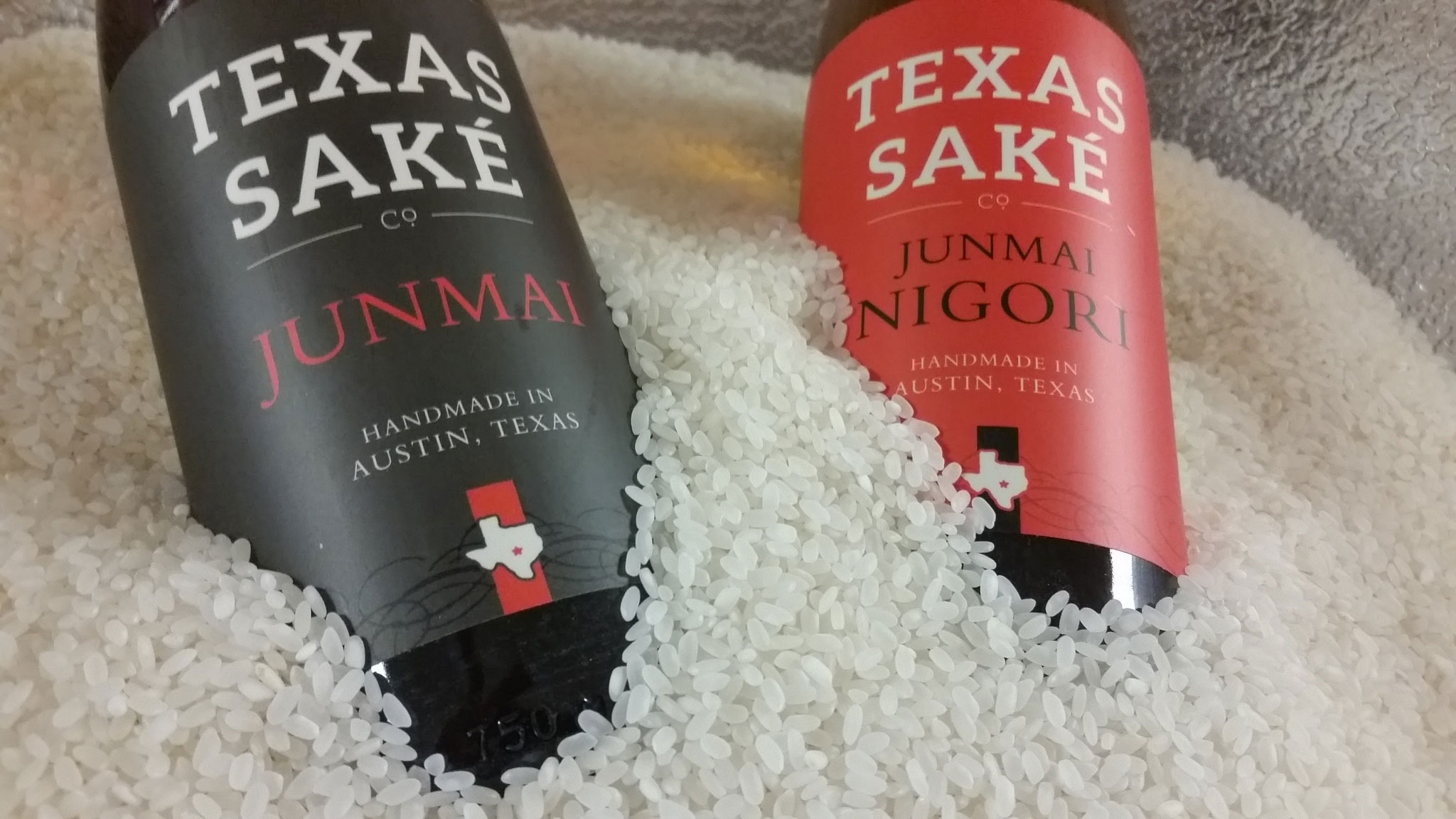 Two bottles of sake surrounded by a pile of white rice