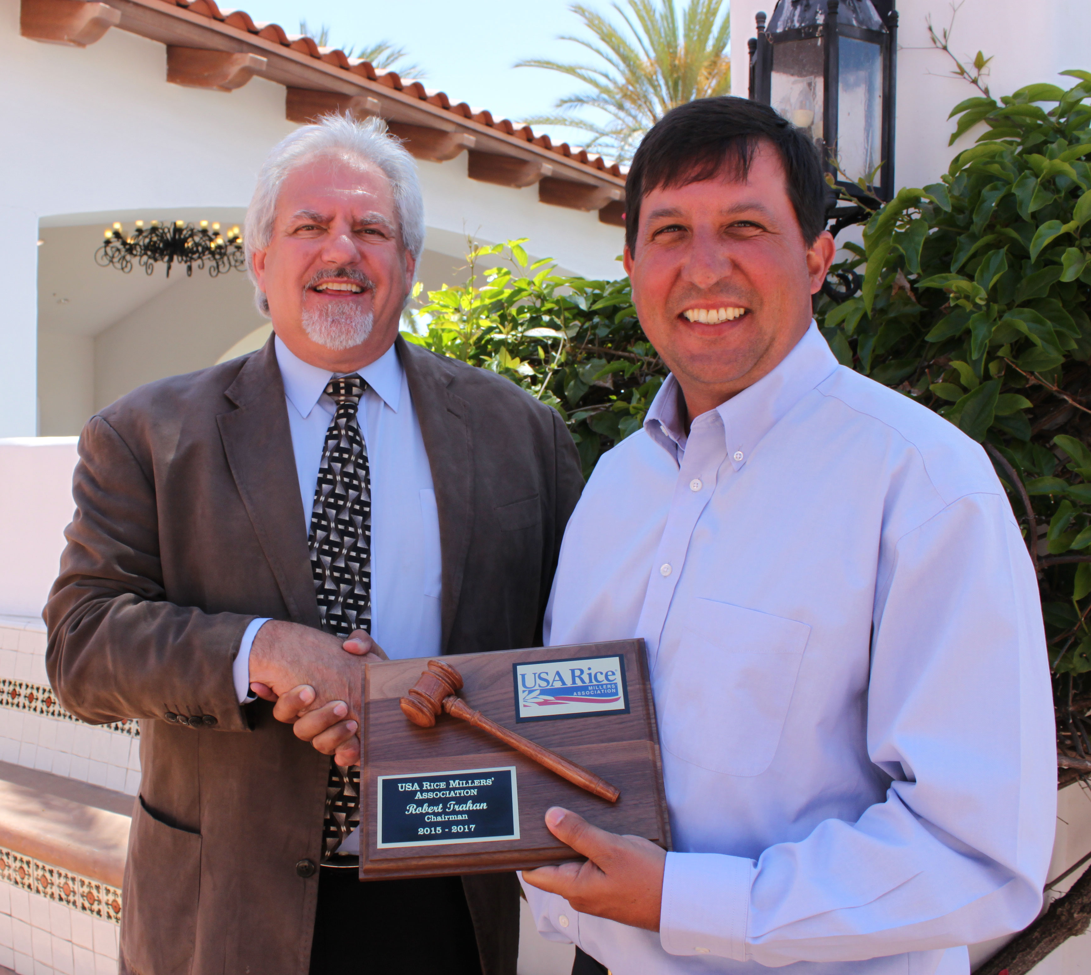 CA miller Alex Balafoutis shakes hands with and gives plaque to LA miller Robert Trahan