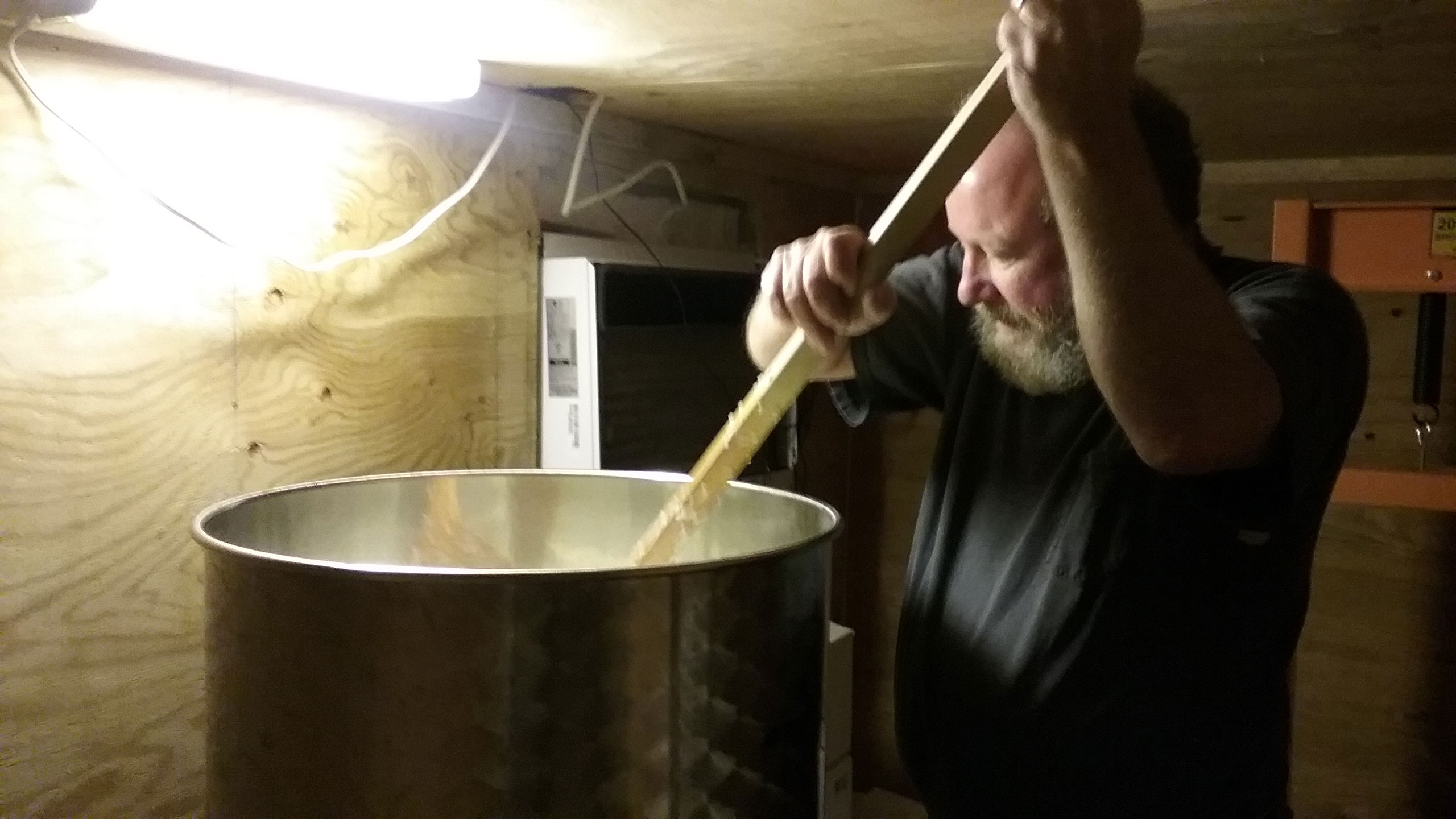 Man brewing sake, stirring large pot