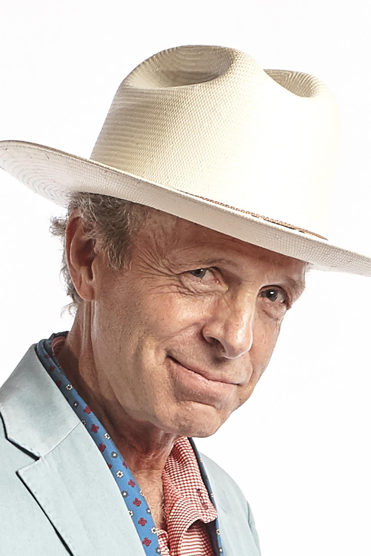 Headshot of journalist Mark McKinnon in large white, straw hat
