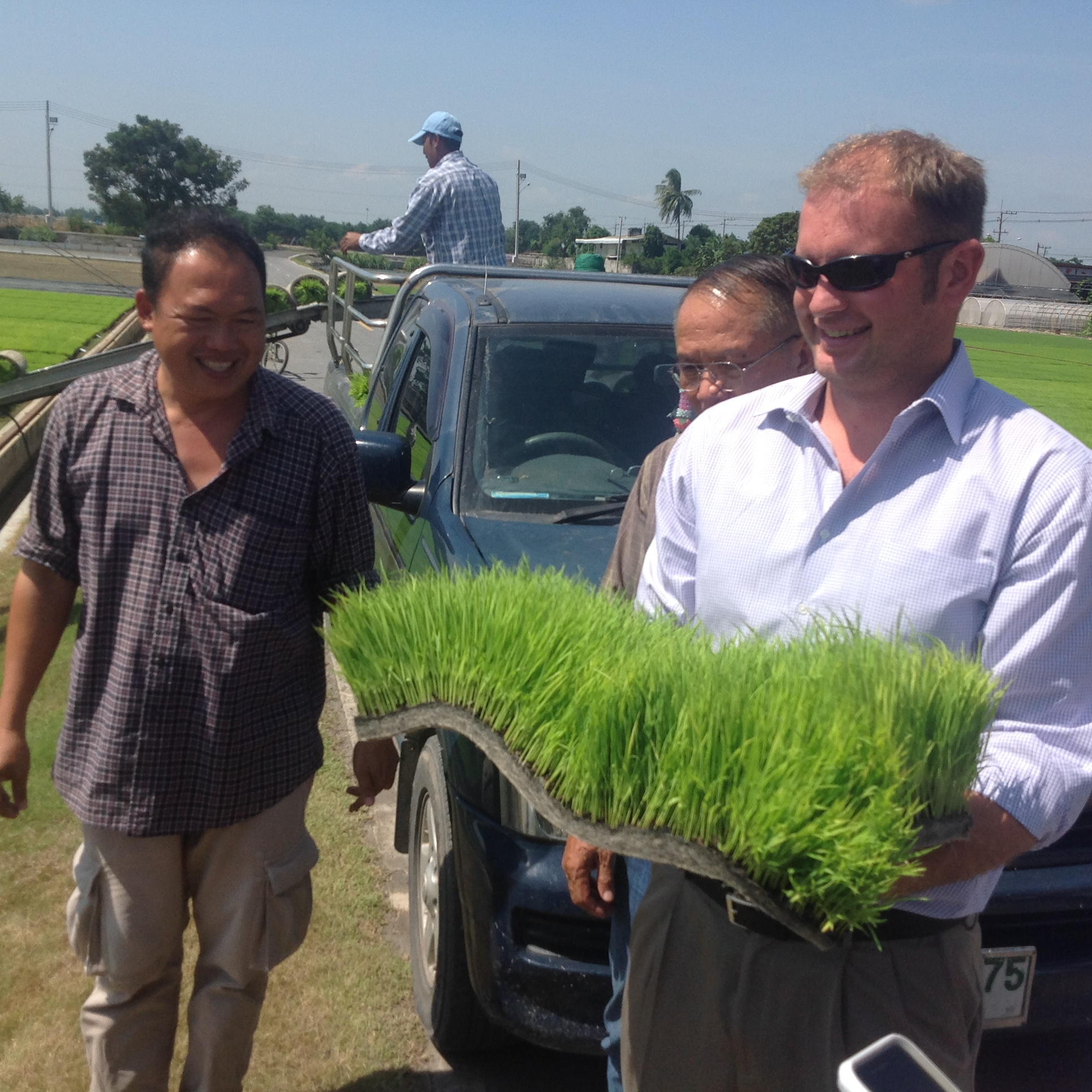 Tim Gertson holding rice research materials on Thailand trip