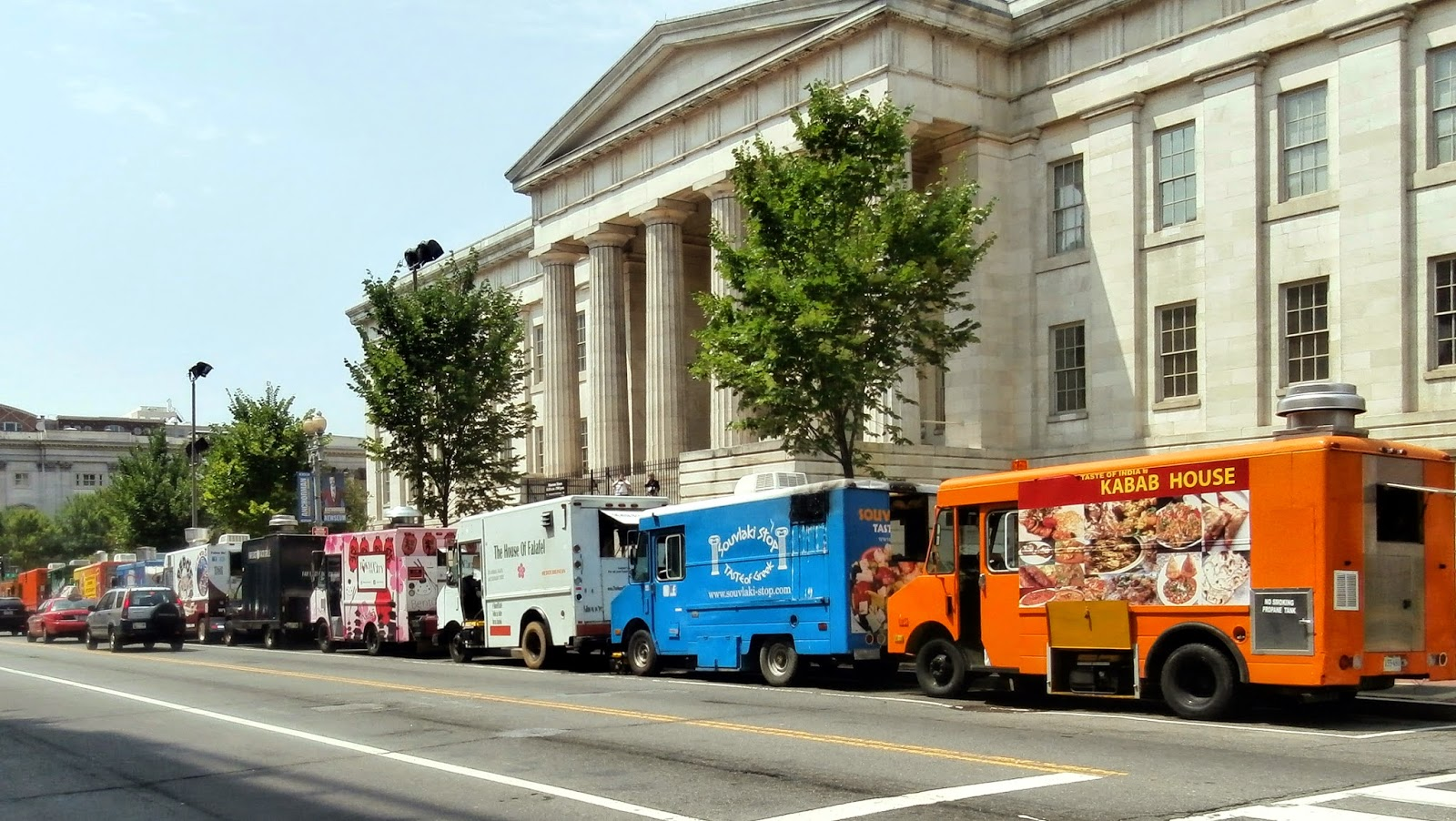 Colorful food trucks parked on the street in front of the National Archives building in Washington DC