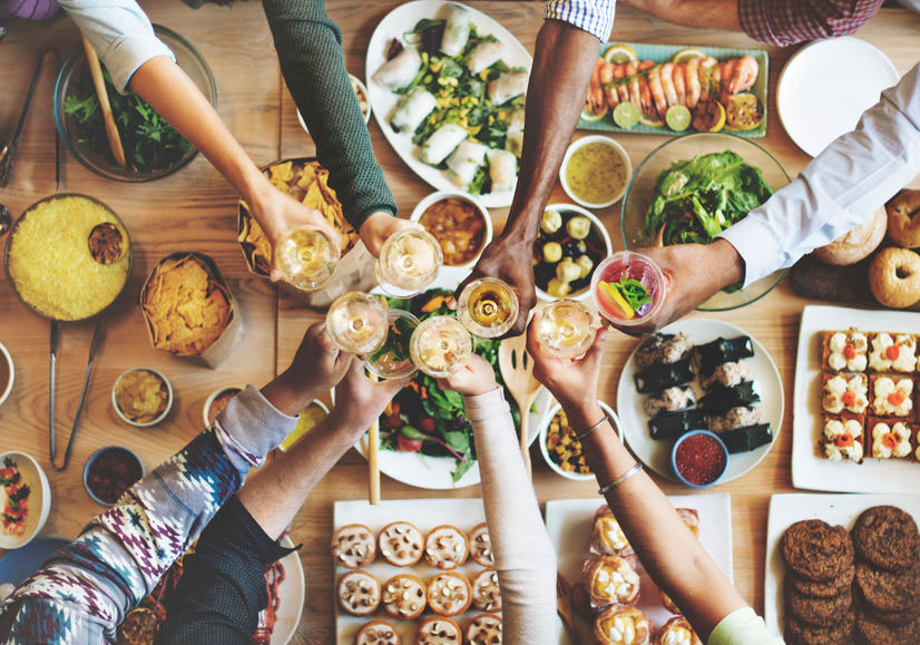 Overhead shot of laden dinner table with manyh hands toasting full glasses of white wine