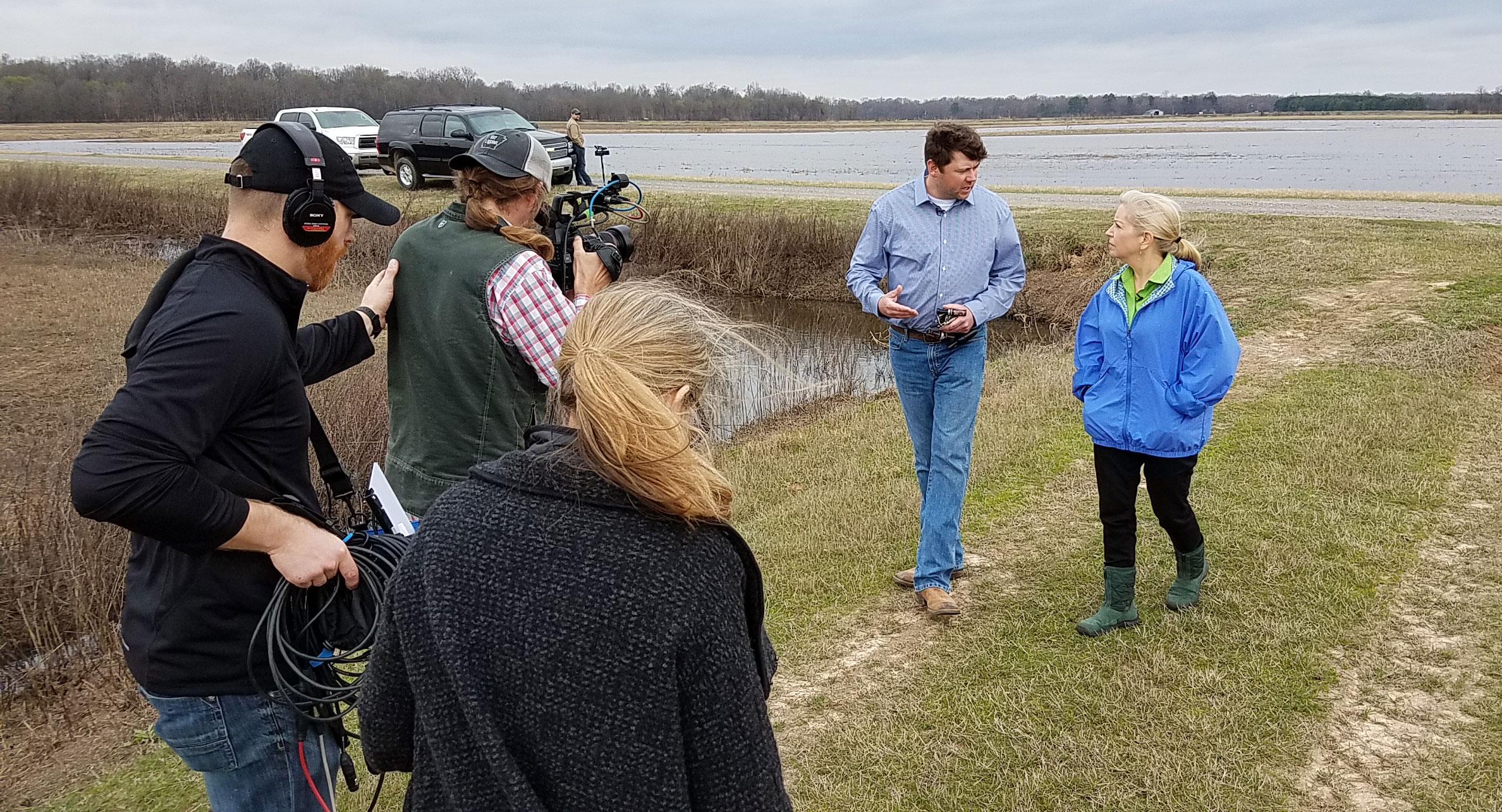 AR Sara-Moulton-Shoot-Sara-&-Eric-Vaught-being filmed by camera crew while walking outside near flooded rice field