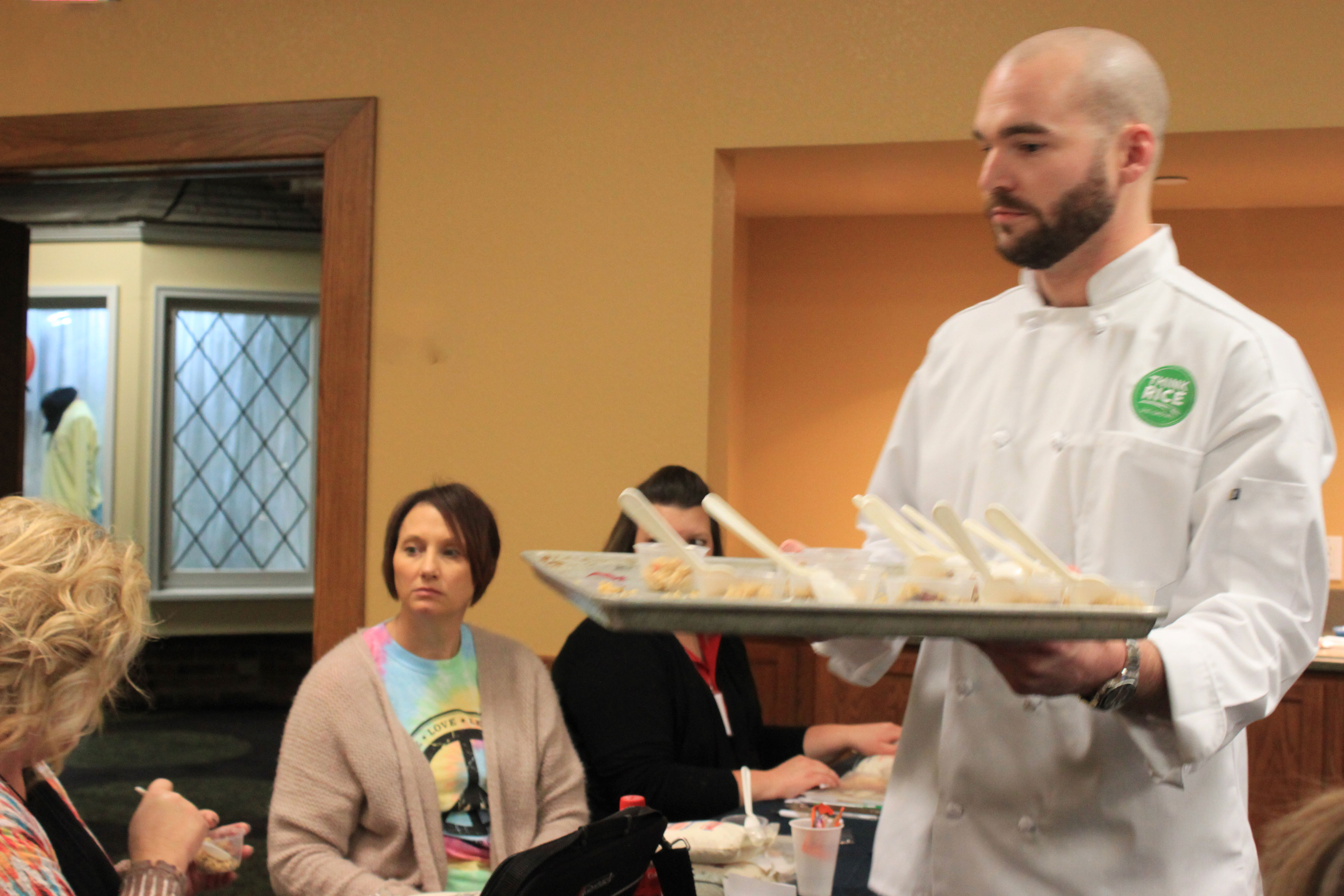 Chef-Charles-Dottore-distributes rice dish samples on a tray to teachers seated at tables