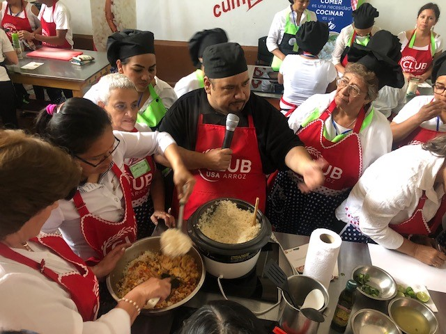 Chef Javier Rodriguez in the middle of a crowd of women wearing red Club Arroz aprons, preparing dish using US rice