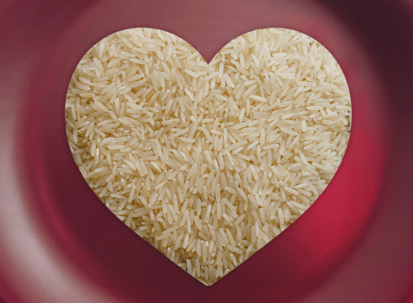 Heart-shaped rice on red background