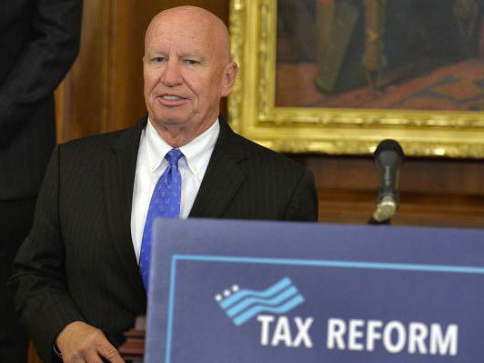 "Rep-Kevin Brady-standing next to podium with ""Tax Reform"" sign"
