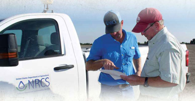 Two men standing near a white pick-up truck with the NRCS logo on the door, one holds a piece of paper and the other is pointing to it