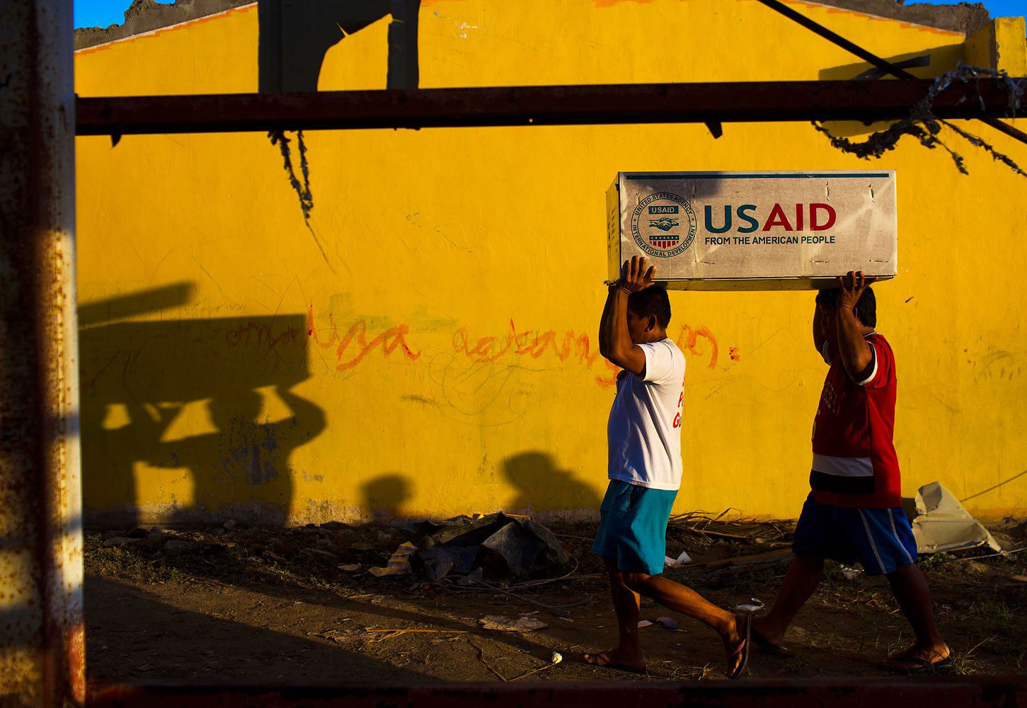 Two men balance a box of USAID food aid on top of their heads