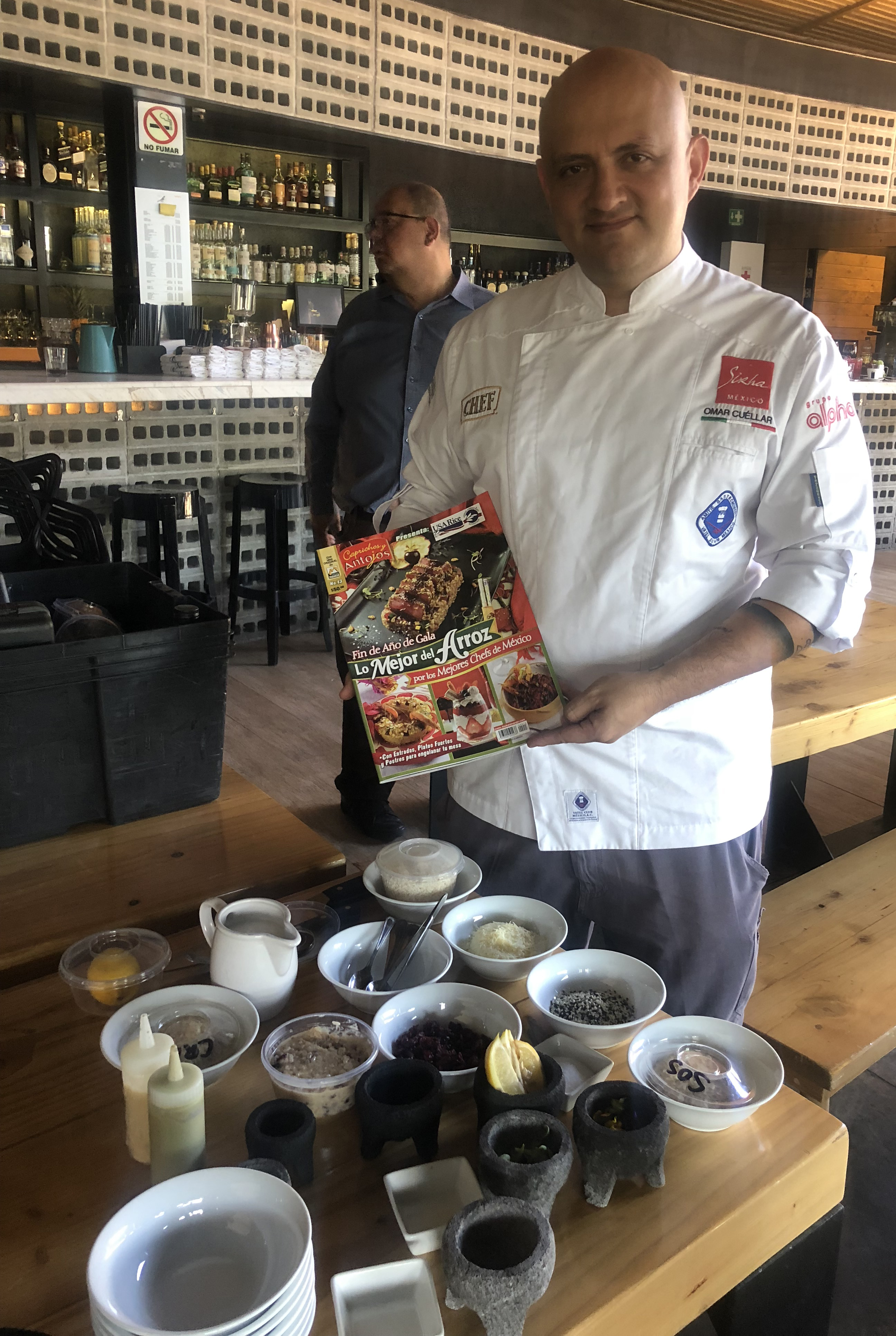 Chef stands in front of table full of ingredients, holding cookbook