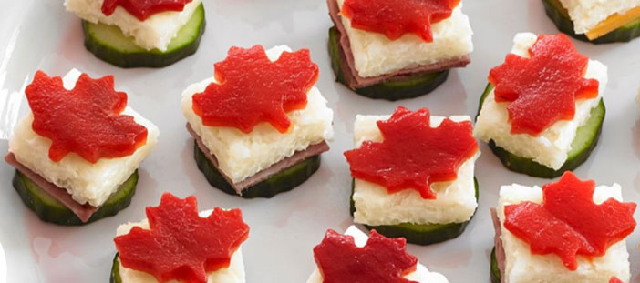 Plate full of bite-sized snacks made with cucumber, rice & red pepper cut in shape of Canadian maple leaf