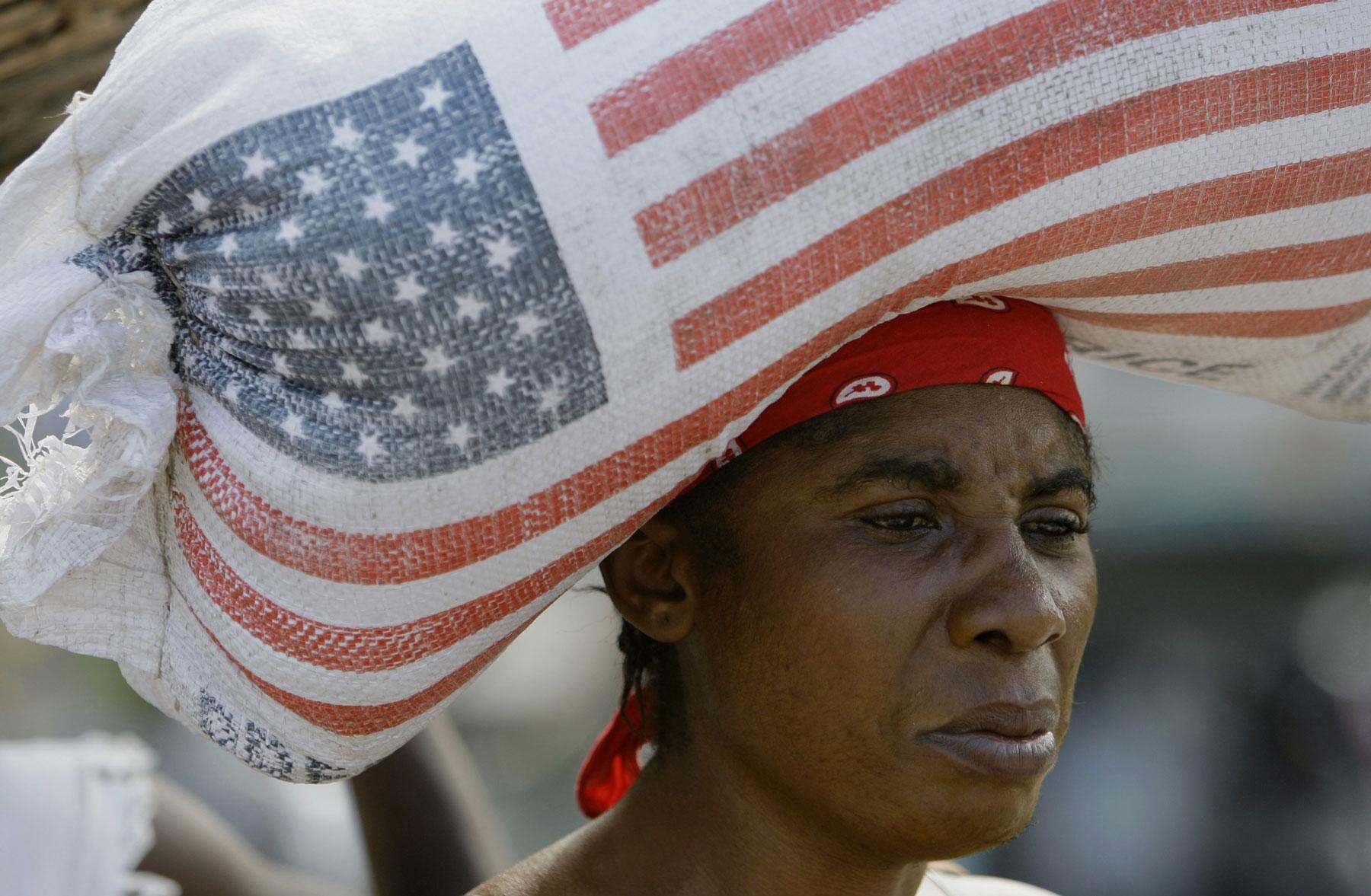 Dark-skinned woman carries bag of US rice on her head