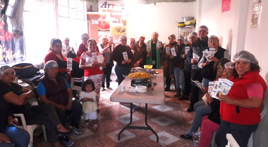 Group shot of seminar participants in Mexican soup kitchen, people in hairnets holding rice pamphlets surround food table