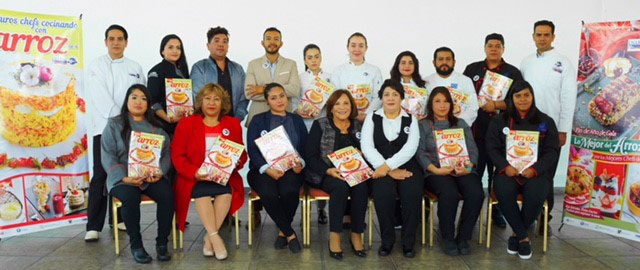 Group shot of chefs and instructors holding Mexican cookbook at launch party 2017