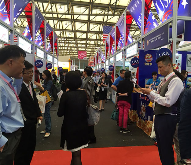 USA pavilion at international trade show, lots of red, white & blue banners and flags with people milling around information booths about US products