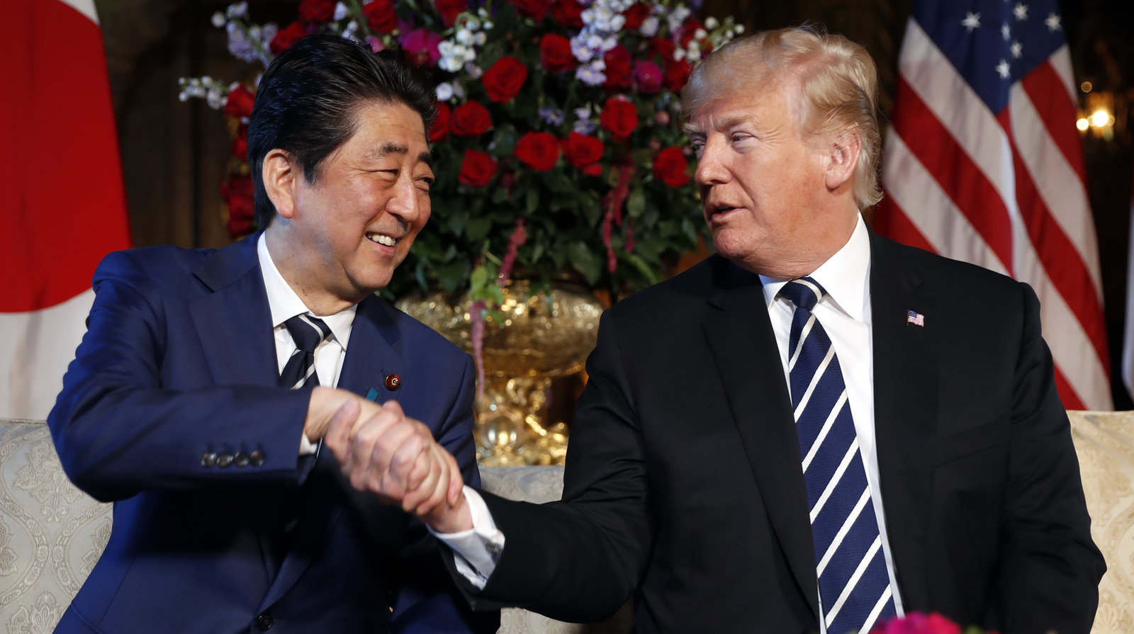 Trump & Japanese PM Shinzo Abe wearing matching blue & white striped ties, shaking hands, sitting on couch