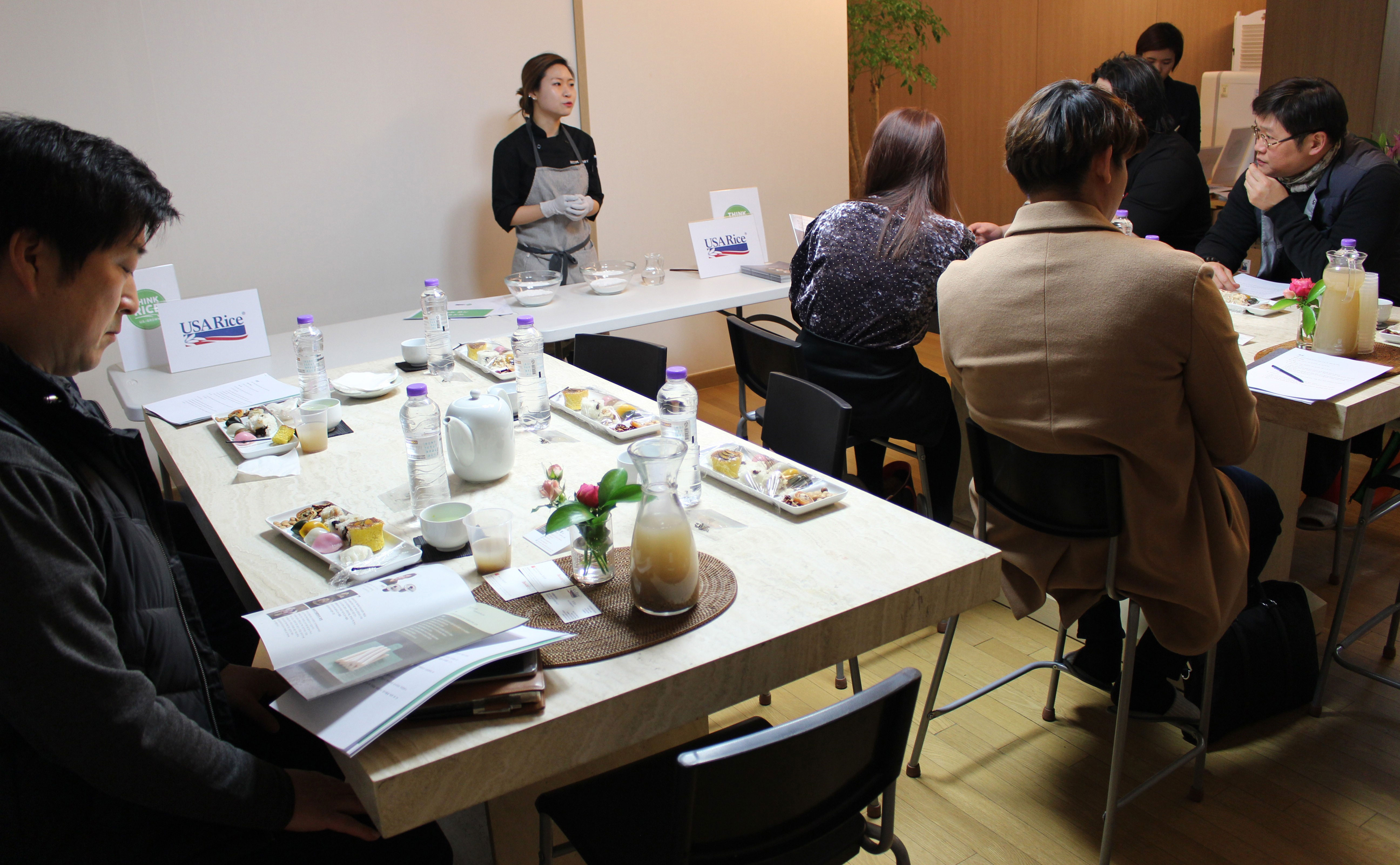 Female chef gives cooking seminar for participants at tables filled with ingredients