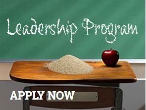 Old fashioned school desk with rice & an apple, Leadership Program written on chalkboard